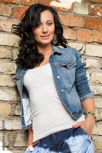 Beautiful young woman at the bricks