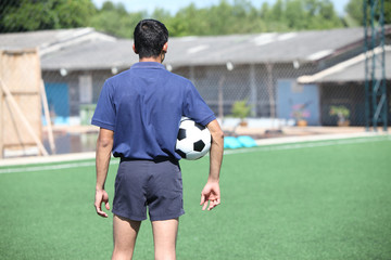 back of a football referee holding the ball