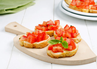 Fresh bruschetta with tomato and basil on cutting board