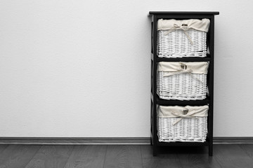 brown shelf with wicker baskets at white wall