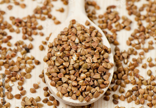 Buckwheat groats in wooden spoon, closeup