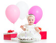 Joyful baby girl with cake, balloons and gifts. Isolated on whit