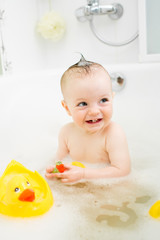 smiling baby girl taking bath and playing with toys