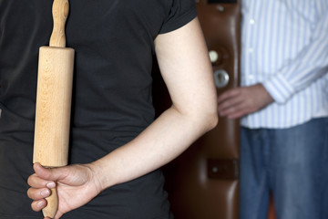 Angry woman with rolling pin waiting for drunk husband