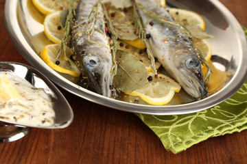 Fish in frying pan with spices and lemon