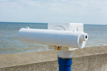 Telescope on seaside promenade.