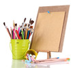 Small easel with sheet of paper with art supplies isolated