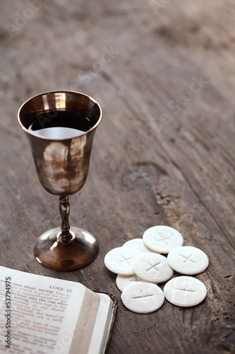 Chalice with wine, bread and open Bible