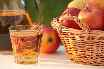 Glass with juice and basket with apples in a garden.