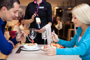 nice dinner in a restaurant - waiter offers wine