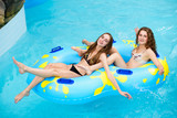 Two smiling women in bikini on the water slide in the aqua park