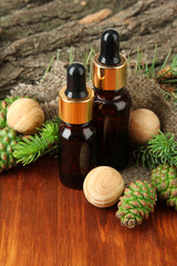 Bottles of fir tree oil and green cones on wooden table