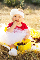 Little baby girl on the nature eating cherry