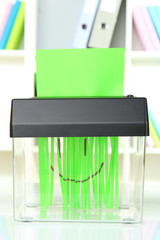 Paper shredder machine, on office interior background
