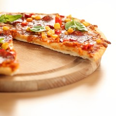 Pizza with salami, corn and herbs on wooden tray.