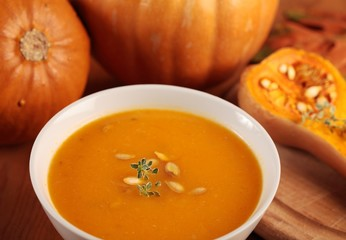 Bowl with pumpkin soup, baked butternut squash and pumpkins