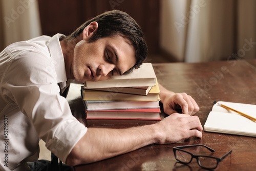 He needs a break. Handsome young author sleeping on the book sta