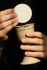 Hands with chalice and communion wafers on black background