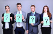Business team standing in row with question mark