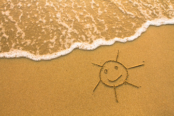 A sun drawn in the sand of a beach.
