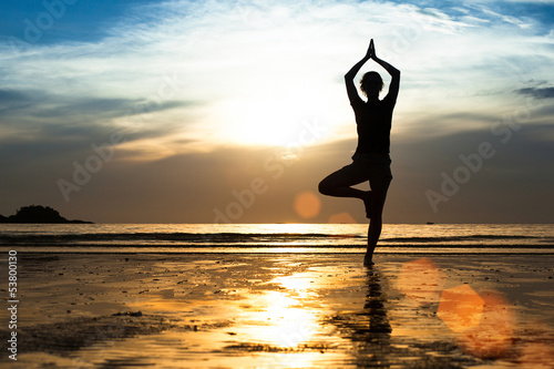 Silhouette of a young woman practicing yoga on the beach.