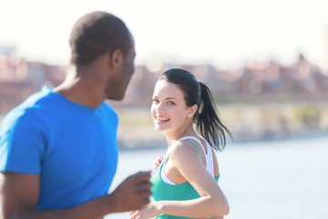Friends meeting. Young couple smiling to each other while joggin