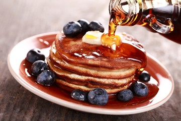 Pouring maple syrup on stack of pancakes
