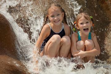 two happy little girls sitting near the pool