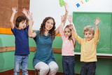 Teacher And Children With Hands Raised In Classroom