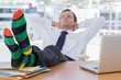 Businessman sleeping with feet on his desk