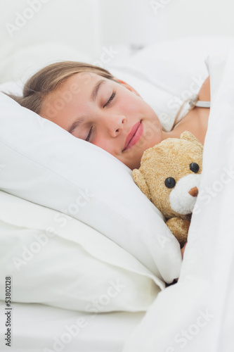 Cute girl sleeping with her teddy bear