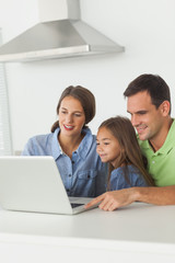 Family using a laptop pc on the kitchen table