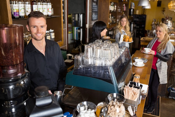 Male Bartender With Colleague Working In Background