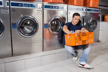 Man With Basket Of Clothes Sitting At Laundromat
