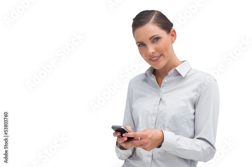 Smiling businesswoman sending text message
