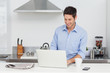 Man using a laptop pc in the kitchen