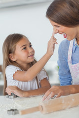 Little girl putting flour on the nose of her mother