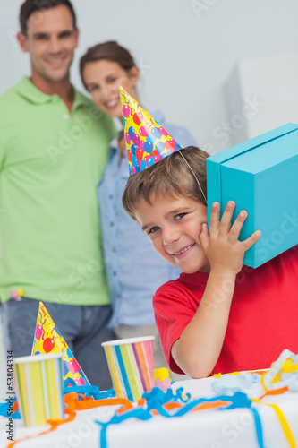 Little boy shaking his birthday gift