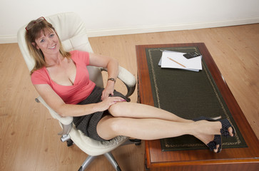Woman sitting at her desk with her feet on the top