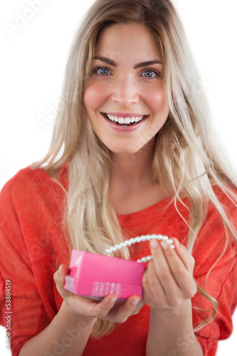 Cheerful woman discovering necklace in a gift box