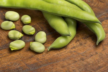 broad beans on wooden background