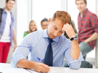 handsome teacher writing in notebook