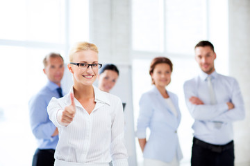 businesswoman in office showign thumbs up