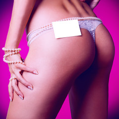 Square photo of female ass in white panties and empty name tag