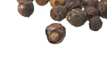 Beans of black pepper close up on white