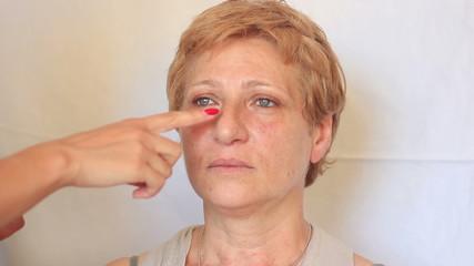 Esthetician - Closeup woman having applied makeup by makeup arti
