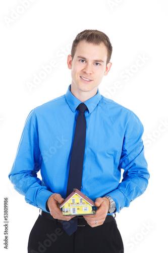 Junger Geschäftsmann hält Miniatur Haus