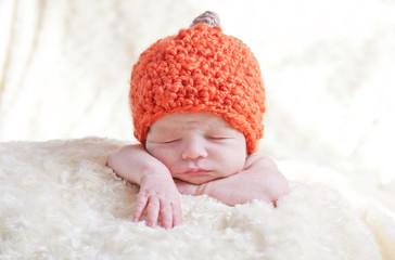 newborn in a cap pumpkin