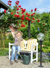 Frau auf der Gartenbank unter Rosen