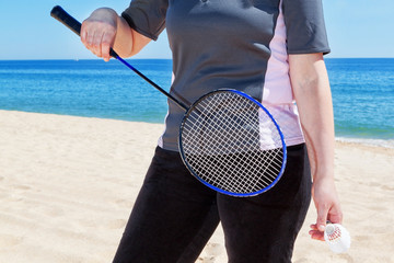 Middle-aged woman playing badminton on the beach. Summer.